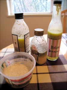 In front: Ranch in an old grated parmesan tub. In back from left to right: Caesar in an old olive oil bottle, Creamy Lemon Poppyseed in an old honey bottle and Italian in an old vanilla syrup bottle.